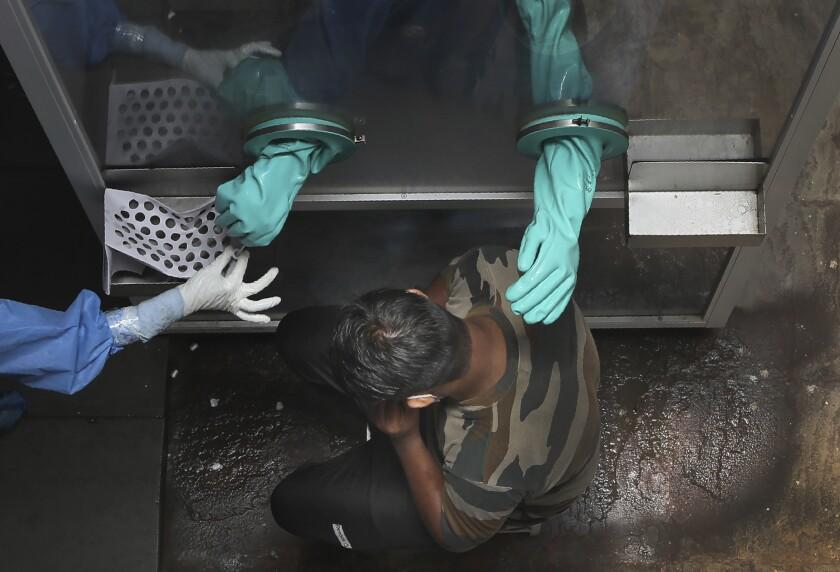 Un trabajador sanitario recoge una muestra de un paciente para una prueba de covid.
