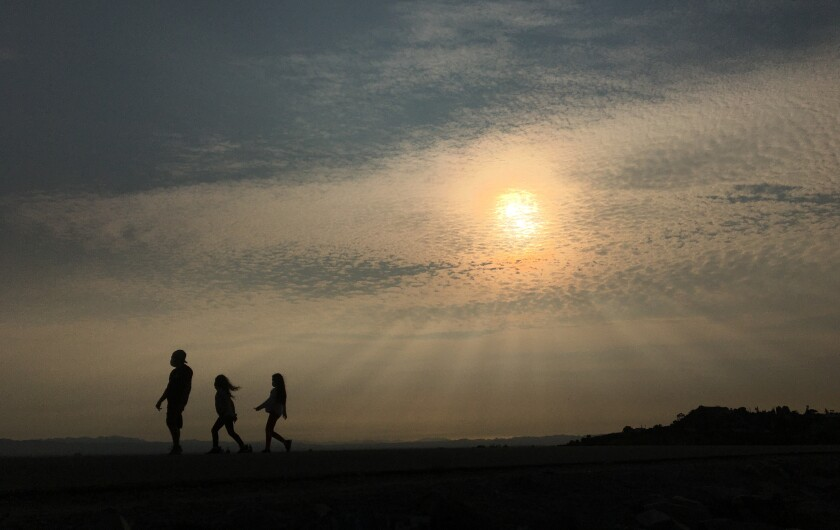 Three people in silhouette are seen walking as sun rays shine through a layer of haze and smoke