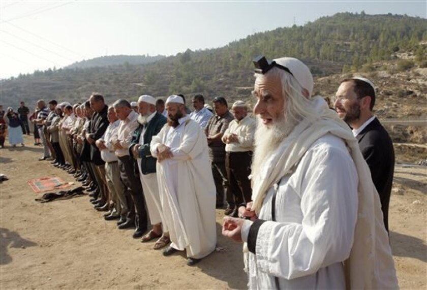 FILE- In this Nov. 11, 2010 file photo, Rabbi Menachem Froman, foreground, prays with Muslim worshippers during a joint Muslim-Jewish prayer for rain near a water spring in the West Bank village of Walajeh. Rabbi Menachem Froman, an Israeli settler known for his efforts to promote coexistence betwe