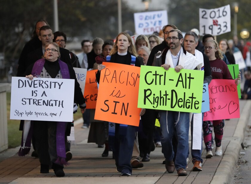 Demonstrators hold signs as they chant outside the Texas A&M; venue where white nationalist Richard Spencer spoke on Tuesday.