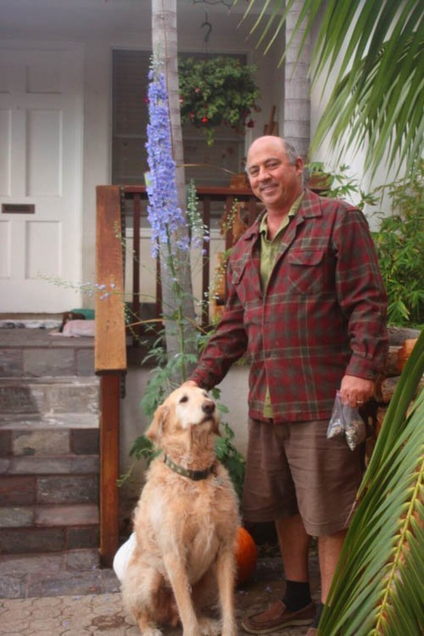 Mark Bucon and his dog, Donner, with bags of poppy seeds to give away in hand. Ashley Mackin photos