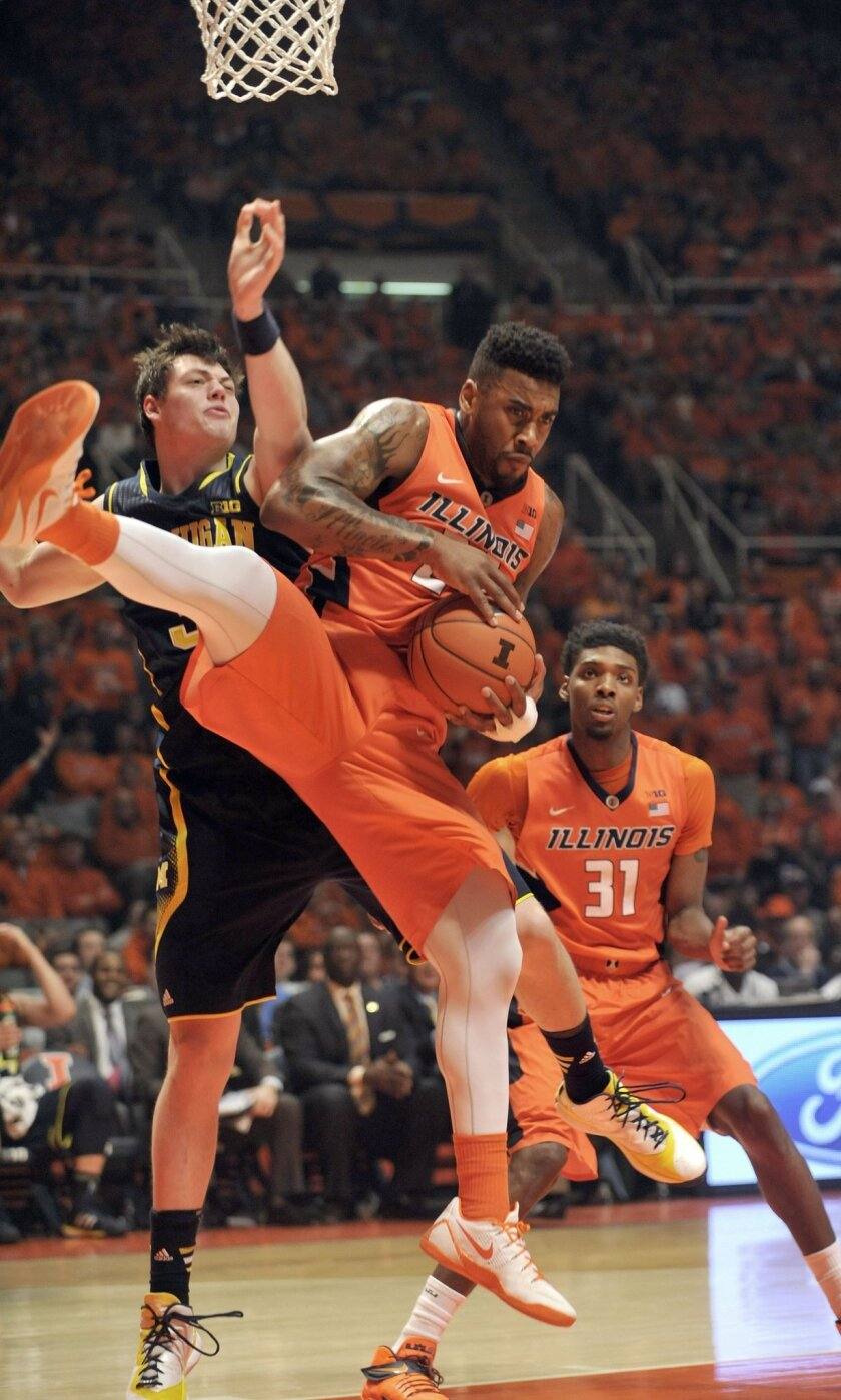 Illinois' Rayvonte Rice (24) pulls down a rebound from Michigan's Ricky Doyle during the second half of an NCAA college basketball game in Champaign, Ill., on Thursday, Feb. 12, 2015. (AP Photo/Rick Danzl)
