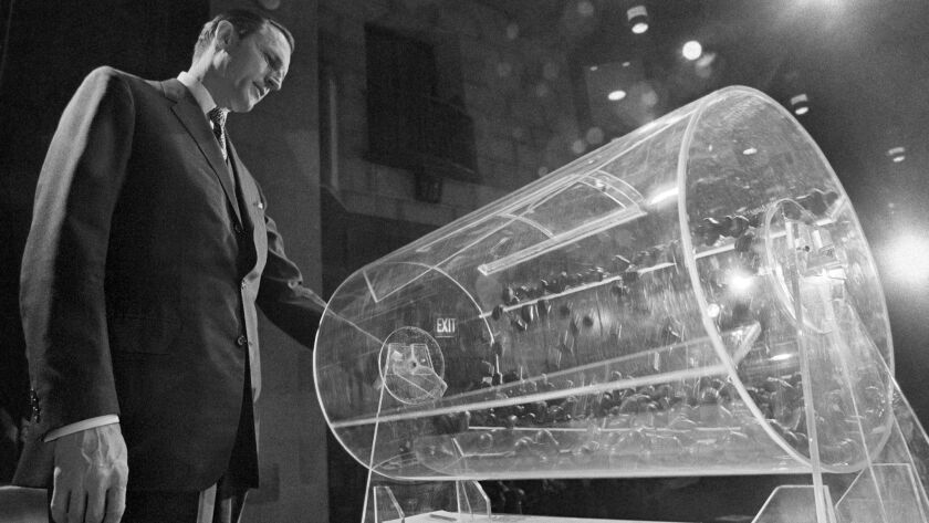 Draft Director Curtis W. Tarr spins a Plexiglas drum during the Selective Service lottery in Washington on Feb. 2, 1972.