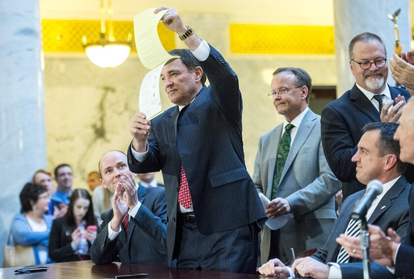 After signing it, Gov. Gary Herbert holds up a copy of a bill at the Capitol, Thursday, March 12, 2015, in Salt Lake City. The bill that protects Utah's LGBT residents while also ensuring religious rights became law amid a cheering crowd that contained both clergy and gay rights activists. (AP Phot
