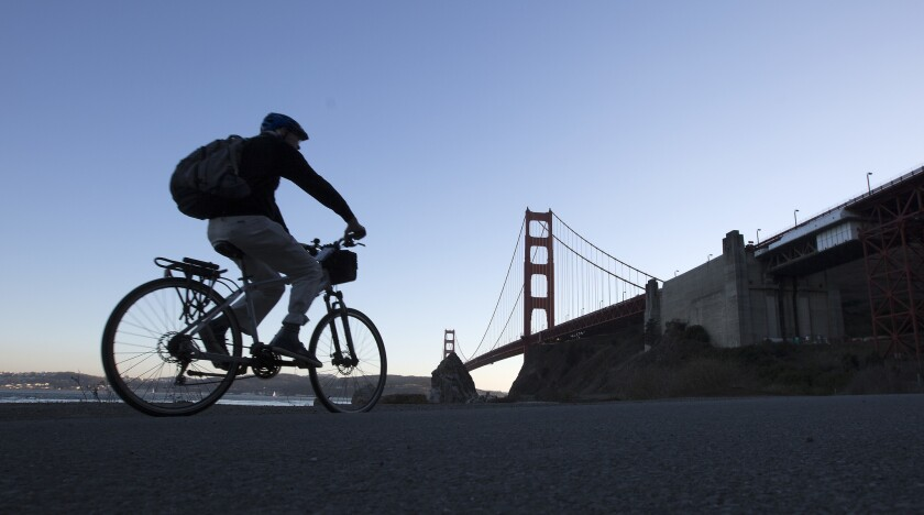 A cyclist rides along a paved road in Fort Baker in the Golden Gate National Recreation Area in San Francisco.