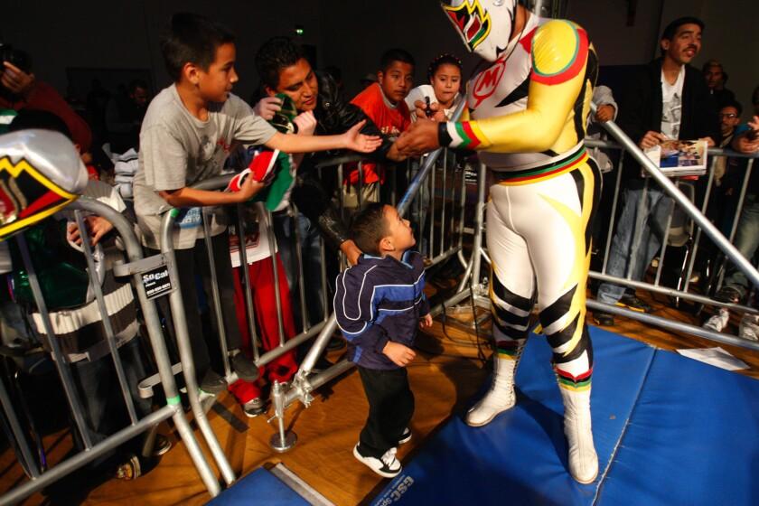 El luchador Mascara Sagrada firma autógrafos durante un evento celebrado al sur de Los Ángeles.