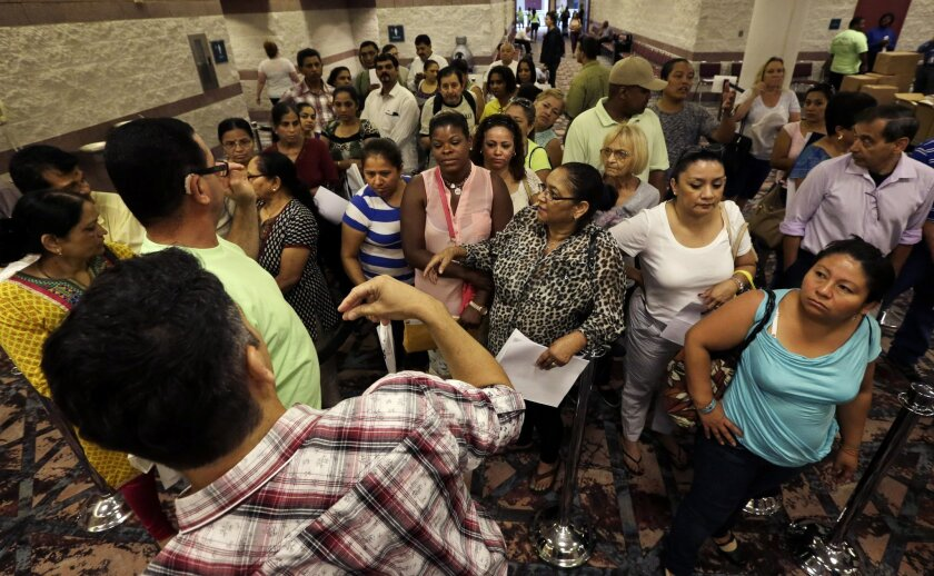 People wait to enter a room to sign up for unemployment at the Atlantic City Convention Center in Atlantic City, N.J. on Wednesday, Sept. 3, 2014. Thousands of newly laid-off casino workers turned out for a mass unemployment filing. The Wednesday morning session comes after a weekend that saw more than 5,000 employees at the Showboat and Revel lose their jobs. (AP Photo/Mel Evans)