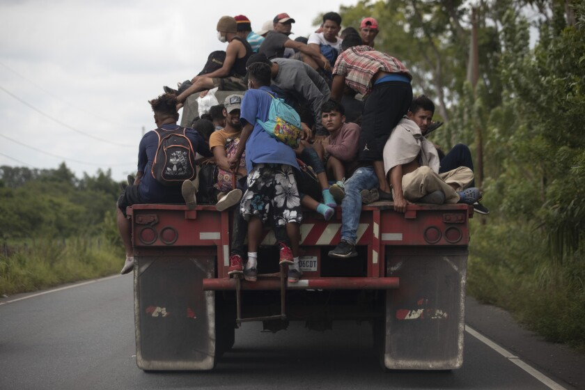 Migrants piled onto the back of a flatbed truck