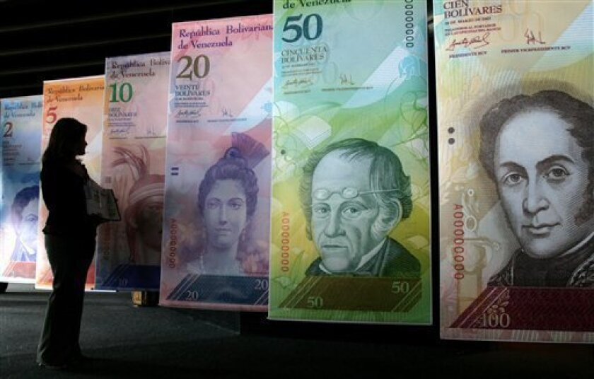 FILE - In this Oct. 24, 2007 file photo, a woman looks at oversized versions of the new Venezuelan currency, coined the 'Strong Bolivar' in Caracas, Venezuela. Thousands of companies suffer under currency controls that all but deny them the U.S. dollars they need to import vital items into this oil