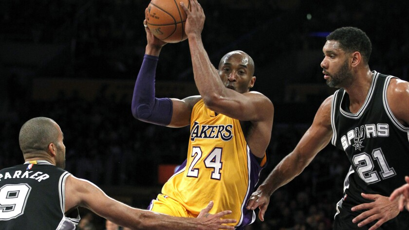 Lakers forward Kobe Bryant (24) drives the lane against Spurs guard Tony Parker (9) and center Tim Duncan (21) during the first half.