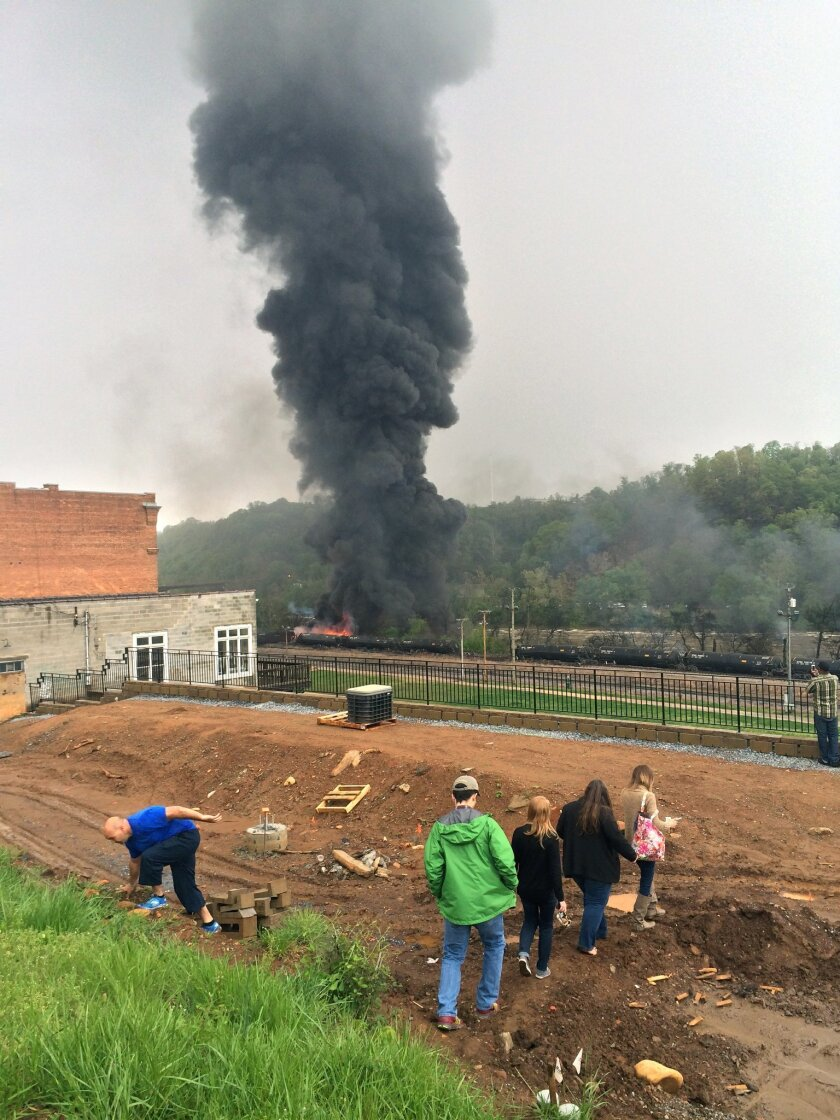 In this mobile phone photo provided Charles Peters, smoke rises after several CSX tanker cars carrying crude oil derailed on Wednesday, April 30, 2014, in Lynchburg, Va. Authorities evacuated numerous buildings Wednesday after the derailment. (AP Photo/Charles Peters) MANDATORY CREDIT