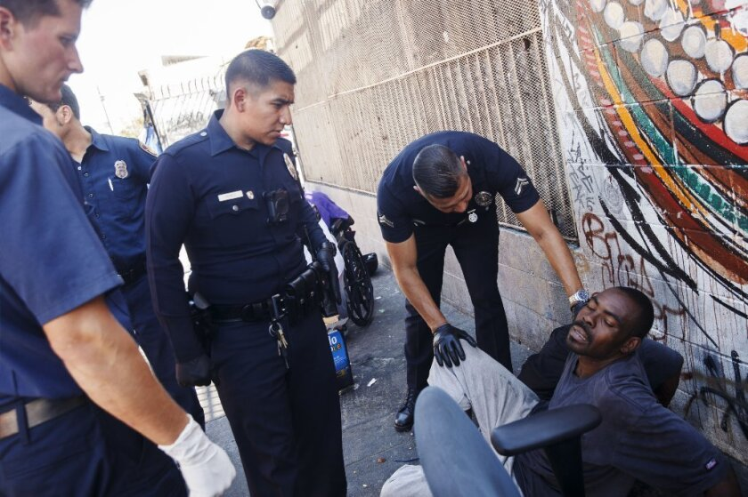 Fire Department personnel provide assistance to a man believed to be feeling the effects of a synthetic cannabinoid called spice on Monday, Aug. 22, 2016, in downtown's Skid Row