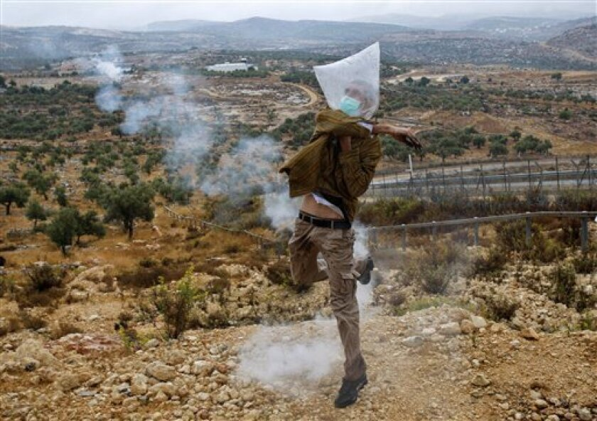 A Palestinian protestor, wearing a plastic bag on his head, throws a tear gas canister back towards Israeli soldiers during a protest against Israel's separation barrier in the West Bank village of Bilin, near Ramallah, Friday, Oct. 30, 2009. (AP Photo/Nasser Ishtayeh)