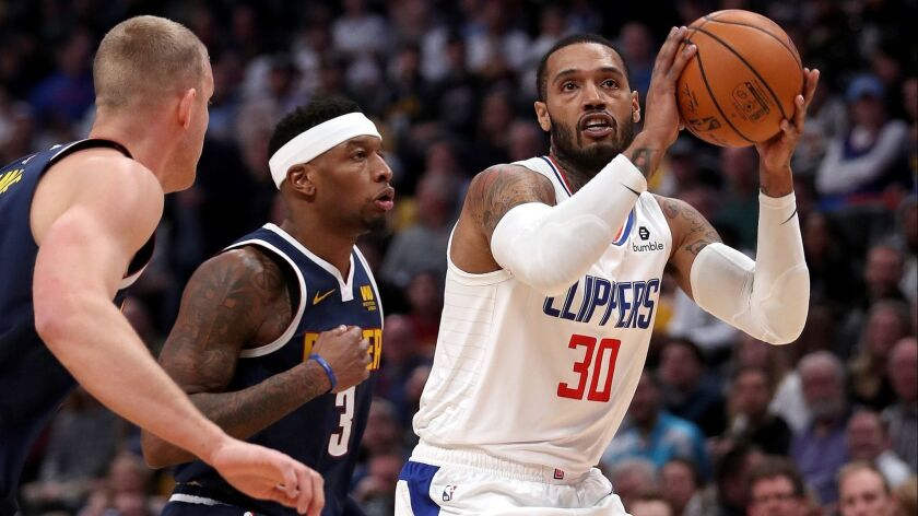 Mike Scott (30) of the Clippers puts up a shot against Torrey Craig (3) and Mason Plumlee (24) of the Denver Nuggets in the first quarter at the Pepsi Center on January 10, 2019 in Denver.