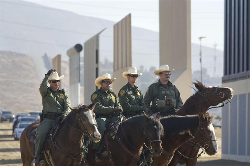 Agentes de la patrulla fronteriza estadounidense posan para los fotógrafos de prensa junto a los prototipos del muro fronterizo entre EE.UU. y México presentados el 26 de octubre de 2017, en San Diego, California (EE.UU.). EFE/Archivo