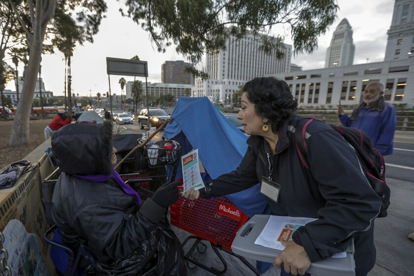 Lisa Pacheco of the Los Angeles Homeless Services Authority, right, gives a leaflet about new rules and restrictions to Alla Gavorkan, 61, who lives in a tent in downtown Los Angeles' El Pueblo historic district.