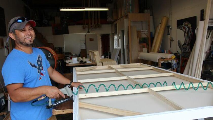 John Lidot of Giant Canvas Co. works on stretching canvas over a frame. (Courtesy photo)
