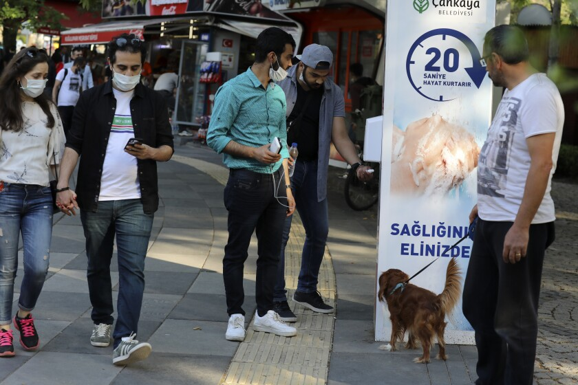 People wearing face masks to protect against the new coronavirus, use disinfectant at the entrance of a public garden, in Ankara, Turkey, Sunday, June 14, 2020. Turkey's President Recep Tayyip Erdogan has revealed Tuesday new plans to ease restrictions in place to curb the spread of the coronavirus, including the July 1 reopening of theaters, cinemas and other entertainment centers.(AP Photo/Burhan Ozbilici)