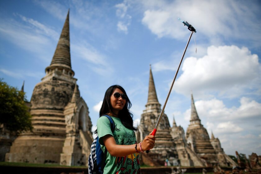A tourist uses a selfie stick to take a photo of herself in the ancient historical city of Ayutthaya, north of Bangkok, Thailand, on Aug. 11, 2015.