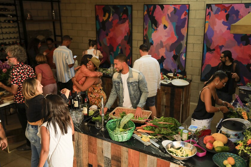 LOS ANGELES, CA., JUNE 9, 2019: The kitchen in Doctors Diego and Resa Caivano's home is buzzing with activity while everyone helps to prepare the Sunday dinner June 9, 2019. The fresh vegetables came from their rooftop garden. The Caivanos love having dinner with their friends so much that it has become a tradition in their hillside Silver Lake home. On any given Sunday as many as 30-50 people are fed grilled delights from their outdoor pizza oven and grill and vegetarian dishes mixed with the fellowship of friends and neighbors. Designed by architect Brooks Atwood, the home reflects the funky, stylish, intelligence of the owners with a nod to practical, natural elements like an edible rooftop garden and a pool that is filtered by plants