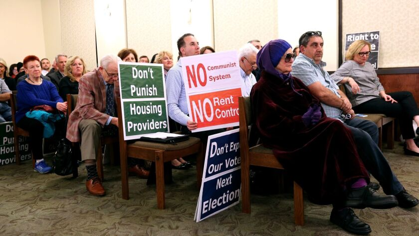 Signs for and against rent control were held inside council chambers at Glendale City Hall during th