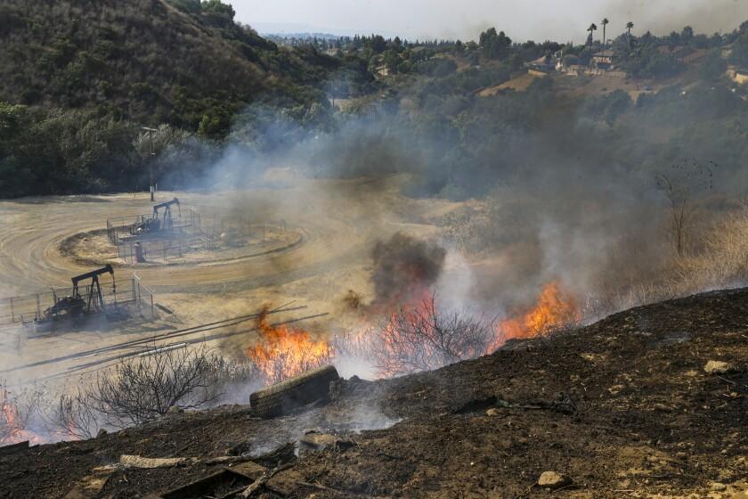 A wildfire burns near oil derricks in Yorba Linda.