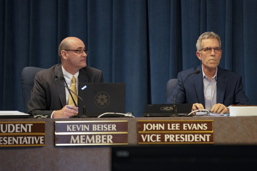 San Diego Unified School District board member Kevin Beiser (left) sits next to member John Lee Evans in April 2019.