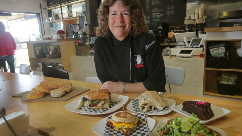 Barbara McQuiston, founder and owner of The Curious Fork cafe, bakery and cooking school in Solana Beach, with some of her gluten-free sandwiches, wraps, breads and desserts.