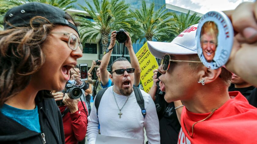Joshua Gonzalez, left, confronts Trump supporter Jake Towe, right, outside the Anaheim Convention Center during a Trump rally.