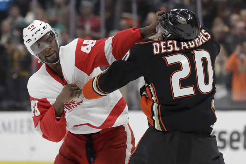 Detroit Red Wings' Givani Smith, left, fights with Ducks left wing Nicolas Deslauriers during the first period on Tuesday at Honda Center.