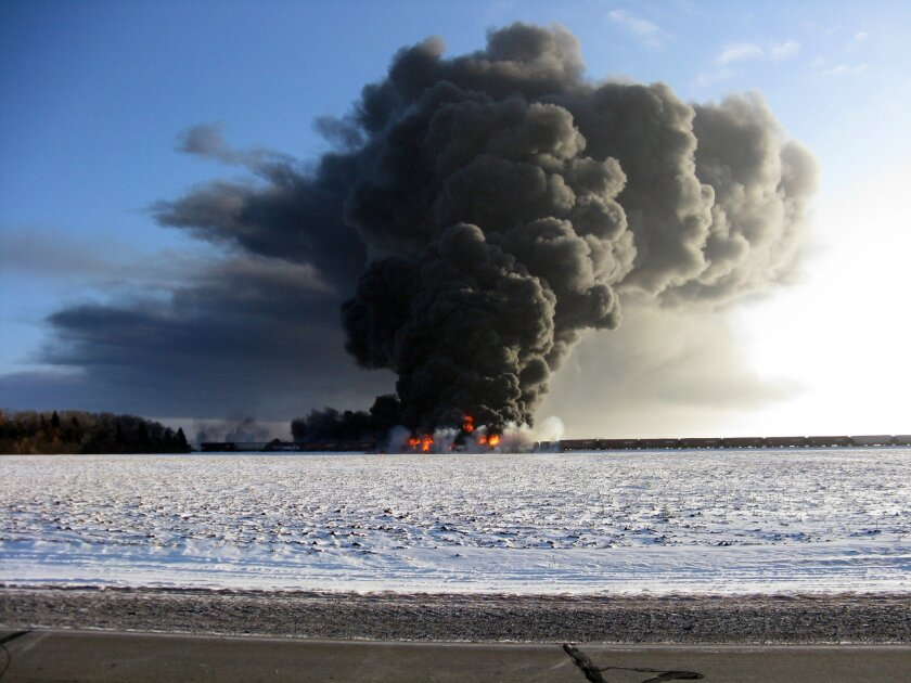 This photo provided by Cass County Commissioner Ken Pawluk shows a train derailment and fire west of Casselton, N.D., Monday, Dec. 30, 2013. No one has been reported hurt in the derailment or fire. By late Monday afternoon, the smoke plume was diminishing and was staying mostly away from town. (AP