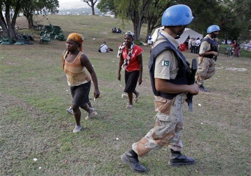 In this photo taken March 14, 2010, two women walk toward the field hospital run by the Jenkins-Penn Haiti Relief Operation, as UN peacekeepers from Pakistan arrive to provide security for the visit of U.N. Secretary-General Ban Ki-moon, at the makeshift camp for earthquake survivors in the Petionv
