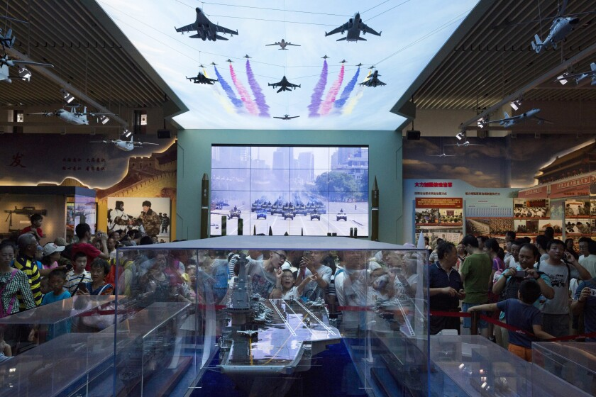 Visitors look at a scale model of a Chinese aircraft carrier