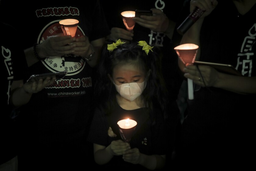 Participants holds candles during a vigil for the victims of the 1989 Tiananmen Square Massacre at Victoria Park in Causeway Bay, Hong Kong, Thursday, June 4, 2020, despite applications for it being officially denied. China is tightening controls over dissidents while pro-democracy activists in Hong Kong and elsewhere try to mark the 31st anniversary of the crushing of the pro-democracy movement in Beijing's Tiananmen Square. (AP Photo/Kin Cheung)