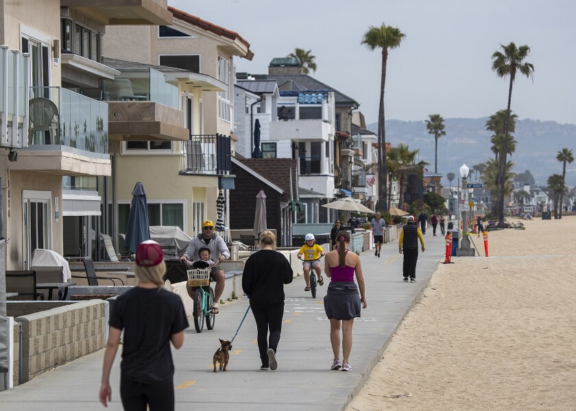 People exercise along the boardwalk near the Newport Beach pier