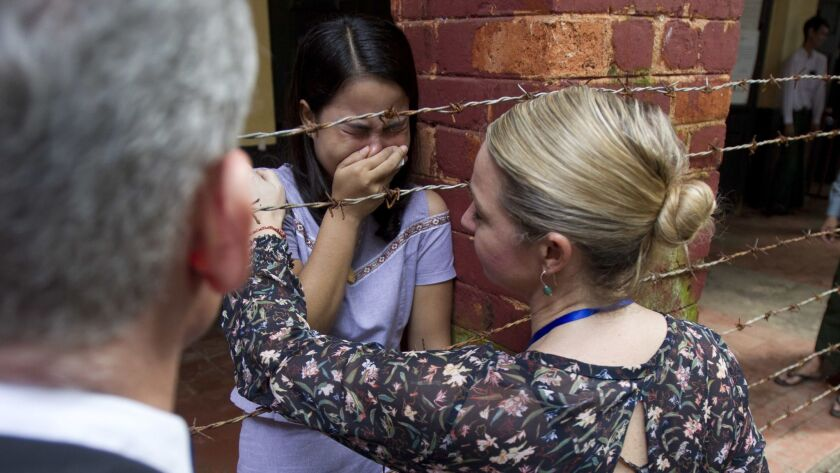 Chit Su Win, center, wife of Reuters journalist Kyaw Soe Oo, is comforted by a Reuters official as t