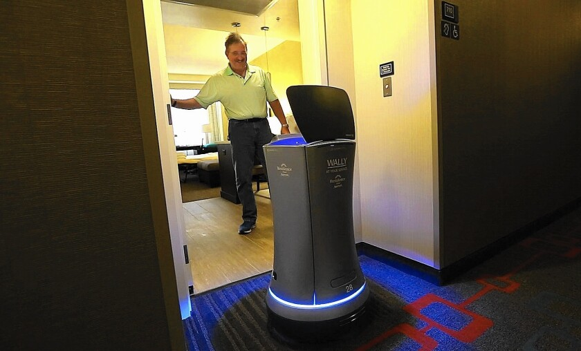 William Savoie of Burlington, Vt., opens the door for Wally, a robot bellhop, as it delivers his order of two bottles of water to his room at the Residence Inn by Marriott on Century Boulevard in Los Angeles. The robot can deliver smaller items such as towels, snacks and coffee to hotel guests.