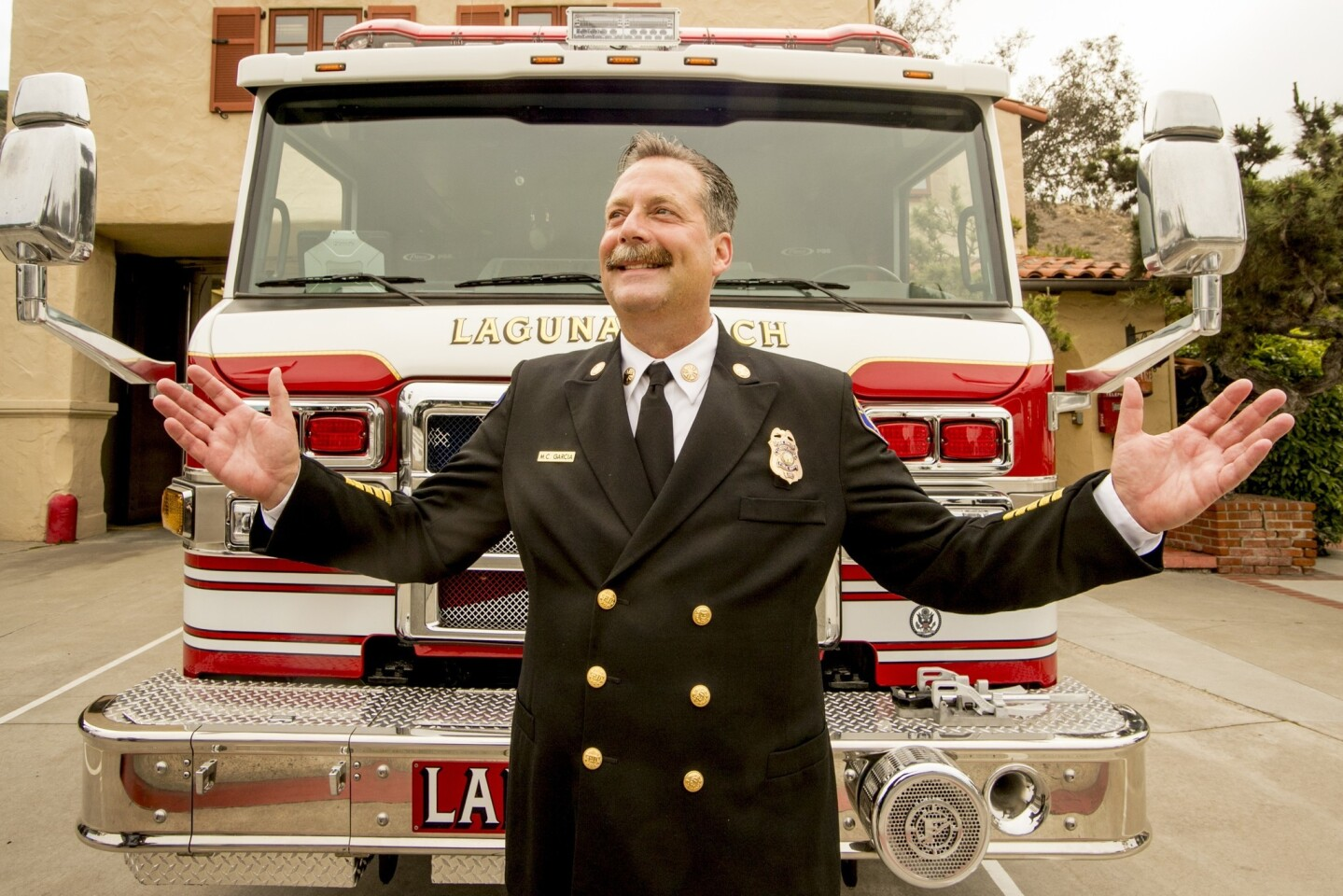 New Laguna Beach Fire Chief Michael Garcia, who took the helm of the department in late April, stands in front of a fire engine after his installation ceremony Monday.