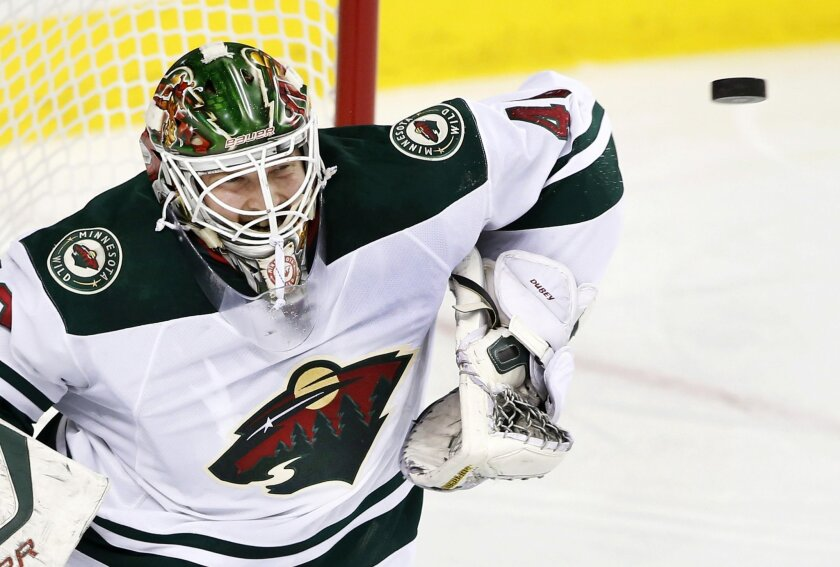 Minnesota Wild goalie Devan Dubnyk makes a save against the Calgary Flames during the first period of an NHL hockey game Wednesday, Feb. 17, 2016, in Calgary, Alberta. (Larry MacDougal/The Canadian Press via AP)