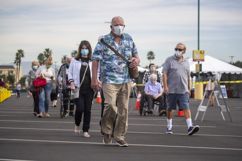 Residents of Orange County wait for COVID-19 shots at the mass vaccination site near Disneyland on Jan. 13.
