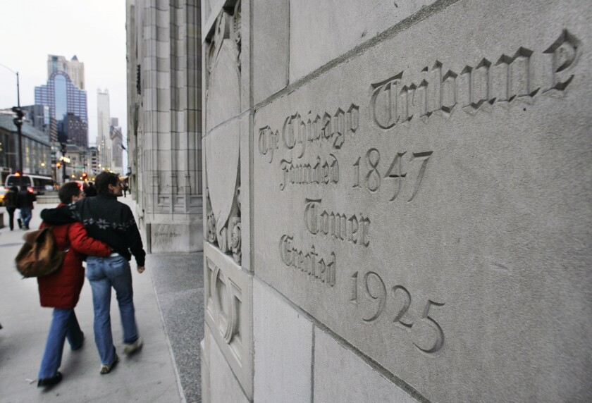 FILE - In this March 30, 2007, file photo, a couple walks past the front entrance to the Tribune Tower, which houses The Chicago Tribune, in Chicago. Tribune Publishing Co., the company that owns the Chicago Tribune and other major U.S. newspapers said Monday, April 5, 2021, that it would discuss a $679 million bid from hotel mogul Stewart Bainum and Wyoming billionaire Hansjörg Wyss that is higher than the $634 million offer from hedge fund Alden Global. (AP Photo/M. Spencer Green, File)