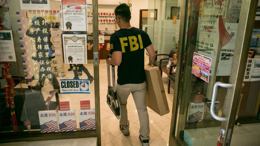 An FBI agent enters the lobby of the California Investment Immigration Fund/Harris Law Group on April 5, looking for evidence of visa.