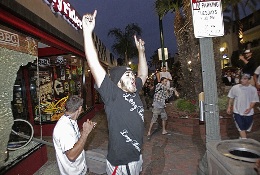 A man appears to celebrate after a stop sign was smashed through the window of a Huntington Beach bike shop.