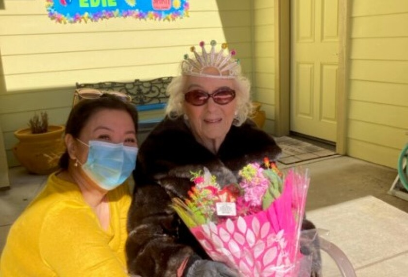 Edie Ceccarelli, right, wearing a tiara and holding flowers, with her caregiver kneeling beside her.