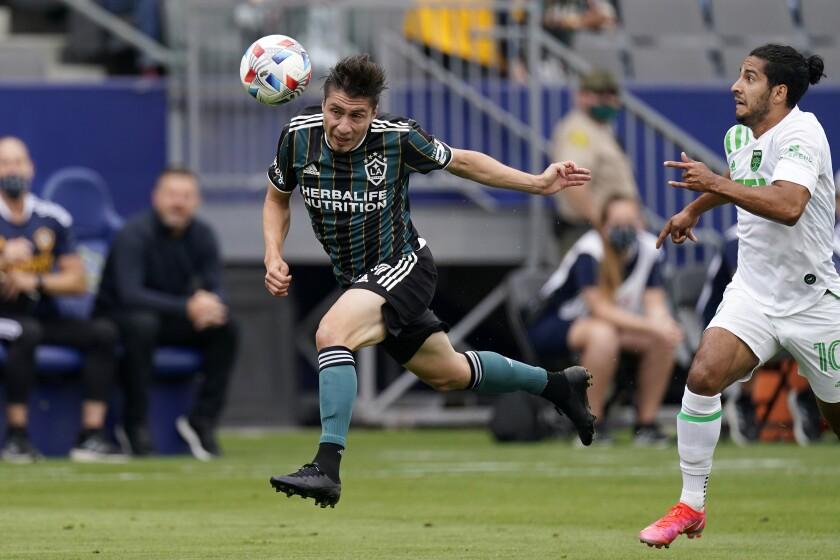 Galaxy defender Jorge Villafaña, left, heads the ball in front of Austin FC forward Cecilio Dominguez.