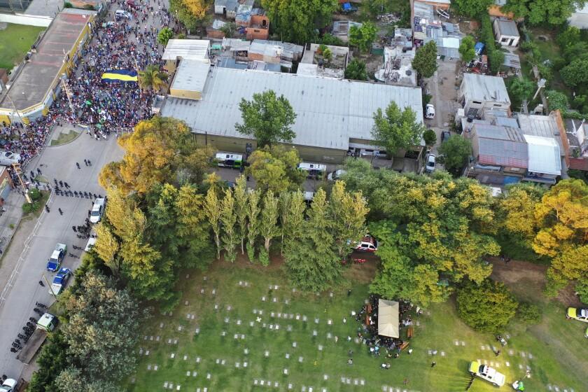 Parientes y amigos de Diego Armando Maradona le dan sepultura, mientras la policía mantiene a raya a una multitud de seguidores en el cementerio Jardín de Bellavista en buenos Aires, el jueves 26 de noviembre de 2020 (AP Foto/Rodrigo Abd)