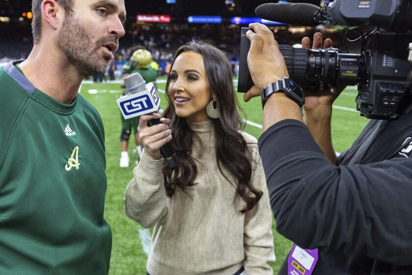 FILE - In this Dec. 14, 2019, file photo, Carley McCord, center, interviews Acadiana head coach Matt McCullough, left, following a win over the Destrehan in the State Division 5A Championship football game in Lafayette, La. Two sports journalists who recently died have been honored in the press box of the Superdome in Louisiana for the College Football Playoff national championship game between Louisiana State and Clemson universities. The Lafayette Daily Advertiser reports seats were reserved in the press box Monday, Jan. 14, 2020, for McCord and Edward Aschoff. (Scott Clause/The Daily Advertiser via AP, File)