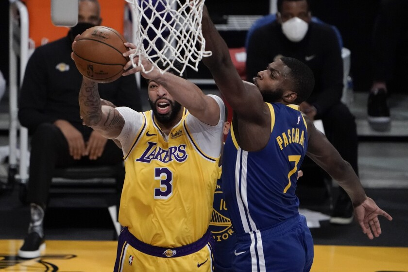 Lakers forward Anthony Davis, grabs a rebound against Warriors forward Eric Paschall.