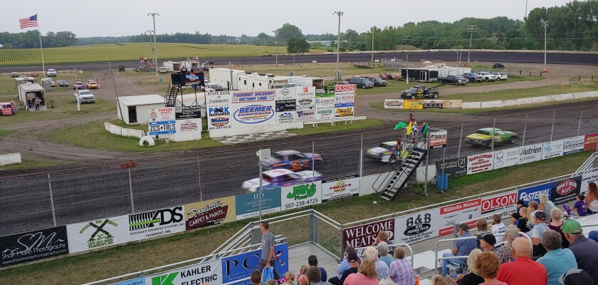 Race cars get the green flag at Fairmont Raceway, Friday, July 23, 2021, in Fairmont, Minn. Lon Oelke, an announcer who was fired by an Iowa track after a racist rant, was back behind the microphone at Fairmont on Friday. (John Reinan/Star Tribune via AP)