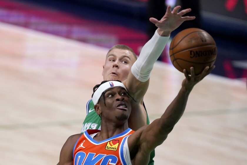Oklahoma City Thunder guard Shai Gilgeous-Alexander, front, gets past Dallas Mavericks center Kristaps Porzingis for a shot during the second half of an NBA basketball game in Dallas, Wednesday, March 3, 2021. (AP Photo/Tony Gutierrez)